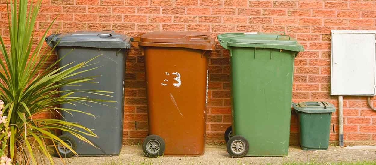 Corby, United Kingdom, 20 june 02019 - traditional wheelie bin in front of a house, brick wall.